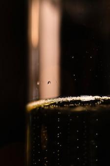 Vidrio de ángulo bajo con champaña en el fondo