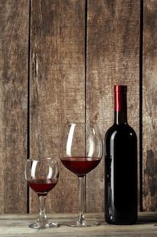 Vidrio y botella con delicioso vino tinto en la mesa contra la mesa de madera