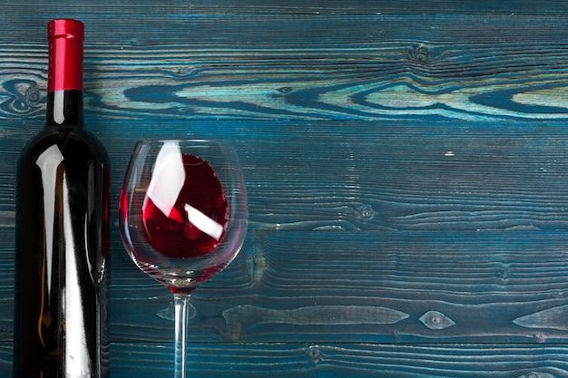 Vidrio y botella con vino tinto sobre fondo de madera, vista superior