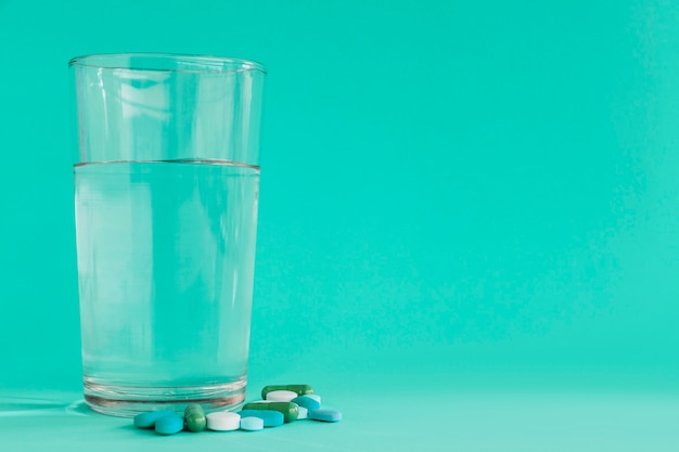 Vidrio claro de agua con pastillas sobre fondo turquesa