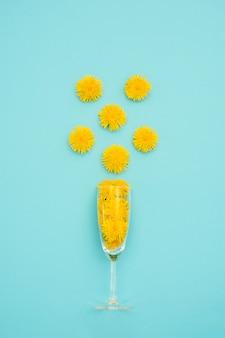 Vidrio con flores de diente de león amarillo en azul