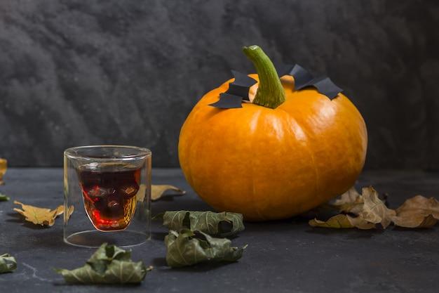 Vidrio en forma de calavera y caída de calabazas de halloween sobre un fondo oscuro.