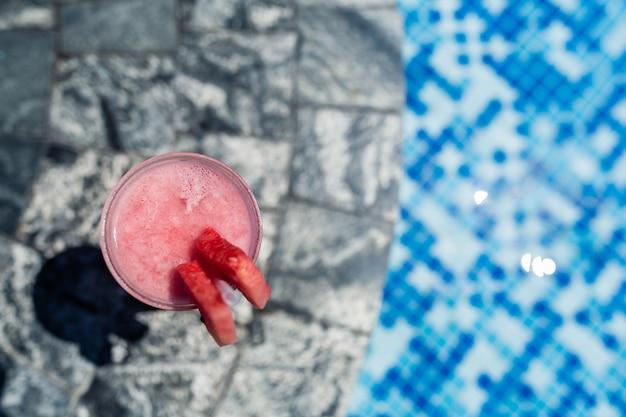 Vidrio fresco de la bebida del smoothie de la sandía que se coloca cerca de piscina