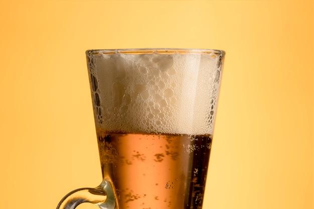 Vidrio fresco de cerveza con espuma sobre fondo amarillo