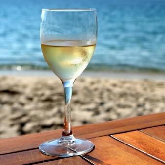 Vidrio frío vino blanco mesa de playa mediterránea cuadrada