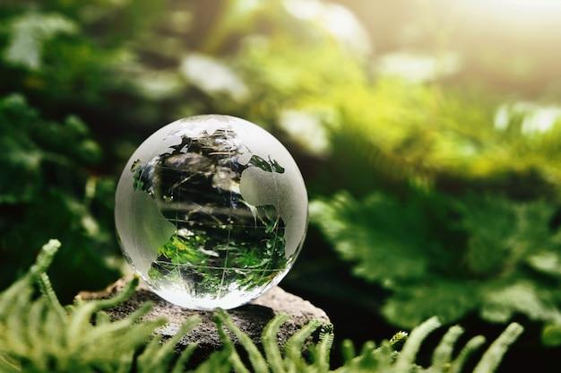 Vidrio de globo de cristal descansando sobre piedra con hojas verdes y sol en la naturaleza. concepto de medio ambiente ecológico