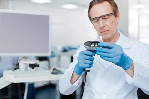 Vidrio protector. trabajador médico competente presionando los labios mientras mira hacia adelante y revisa la sangre
