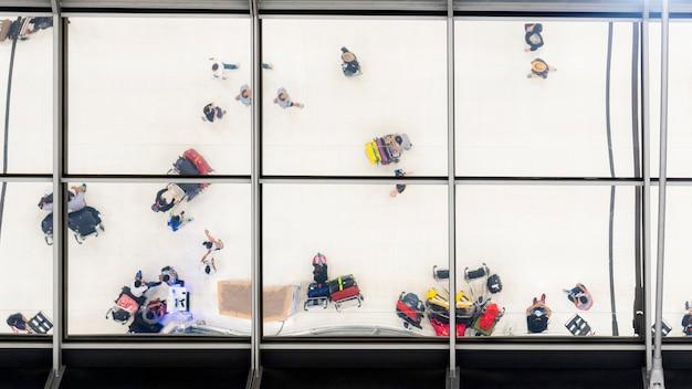 Vidrio de reflexión de personas de vista superior que caminan y se sientan en un banco con equipaje y maletín para viajar en el aeropuerto
