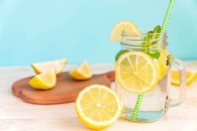 Vidrio del tarro de albañil de limonada hecha en casa con los limones, la menta y la paja del libro verde en la tabla rústica de madera y el fondo azul.