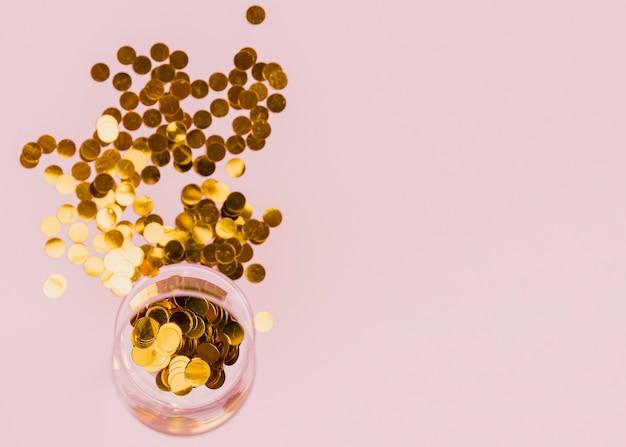Vidrio transparente con confeti dorado en la fiesta