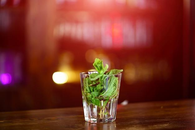 Vidrio transparente con las hojas de menta verde en agua sobre la mesa de madera.