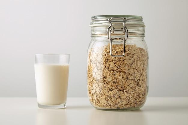 Vidrio transparente con leche orgánica fresca cerca de tarro rústico con copos de avena aislado en el centro de la mesa blanca
