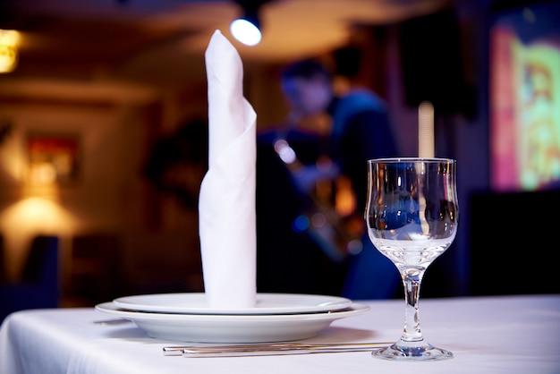 Vidrio vacío en una tabla servida en un fondo borroso un músico con el saxofón en un restaurante acogedor.