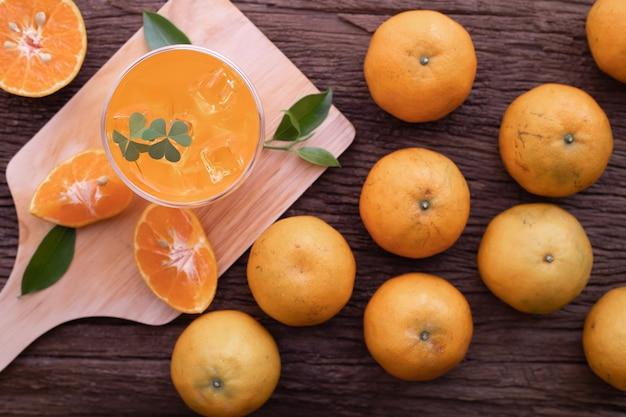 Vidrio de zumo de naranja frío en la tabla de madera.
