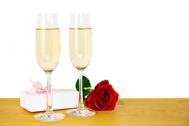 Vidrios de champán con la flor color de rosa y la caja de regalo del día de tarjetas del día de san valentín aislada.