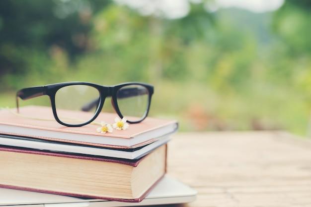Vidrios de libros y de los ojos para leer y escribir sobre la naturaleza borrosa outd