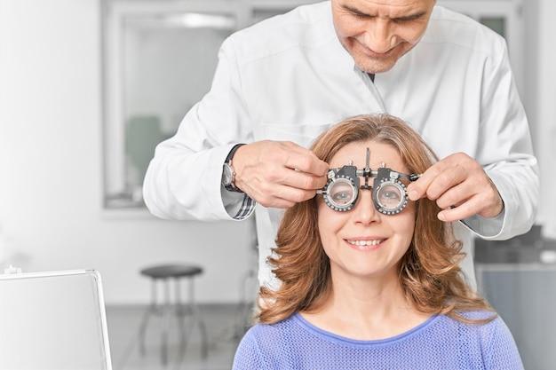 Vidrios que llevan de la mujer con la lente para comprobar la visión.