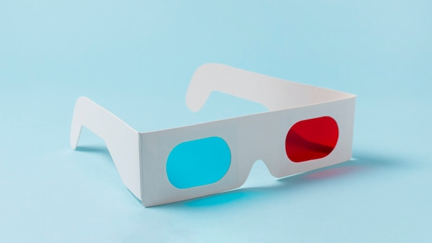 Vidrios rojos y azules del papel blanco 3d en fondo azul