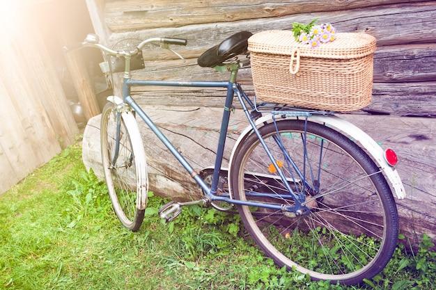 Una vieja bicicleta con una canasta de flores en el jardín de la aldea