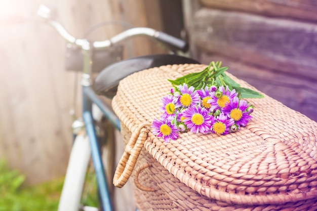 Una vieja bicicleta con una canasta de flores en el jardín está de pie junto a la valla