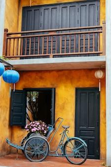 Una vieja bicicleta con flores en una canasta en el fondo de una vieja pared .jardín decoración del hogar.una vieja bicicleta contra la pared en el jardín.vietnam