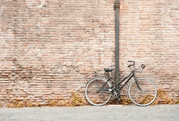 Vieja bicicleta negra contra una pared de ladrillos