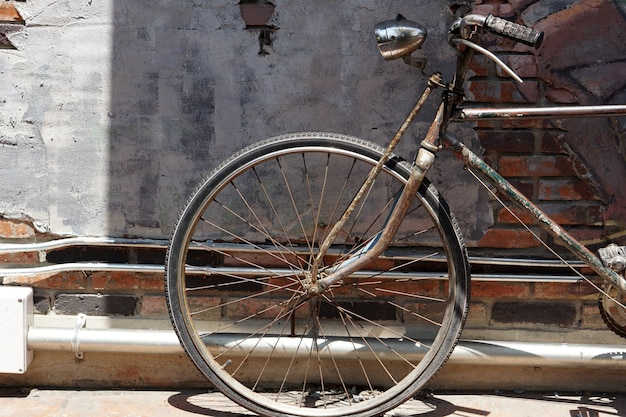 Vieja bicicleta oxidada negra frente a la vieja pared de ladrillos de cemento