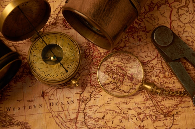 Una vieja brújula con un reloj de oro y una trompeta vergonzosa sobre un mapa de papel