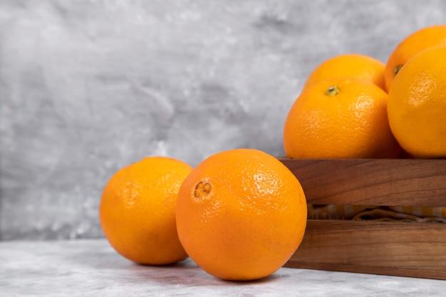 Una vieja caja de madera llena de frutas naranjas enteras y en rodajas colocadas sobre mármol