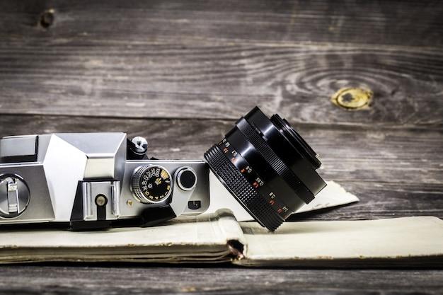 Vieja cámara en el libro vintage, fondo de madera