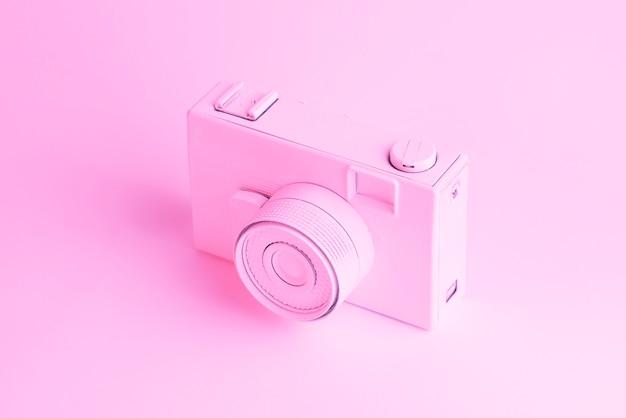 Una vieja cámara vintage contra fondo rosa