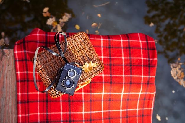 La vieja cámara yace sobre una maleta sobre una manta roja a cuadros. puente de madera cerca del lago.