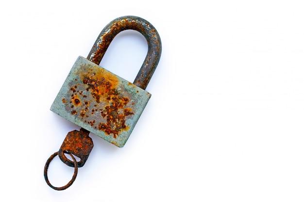 Vieja cerradura oxidada y llave en el fondo blanco.