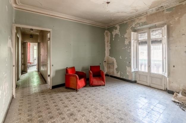 Vieja habitación vacía con sofás rojos.