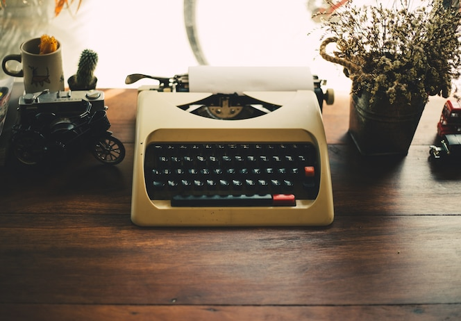 Vieja máquina de escribir en la vieja mesa de madera