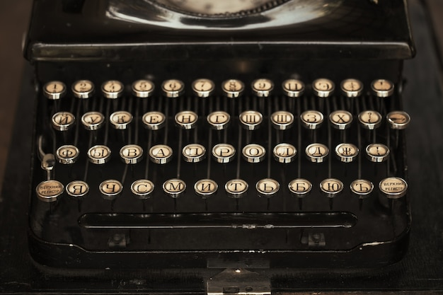 Vieja máquina de escribir negra con papel que vale sobre la mesa