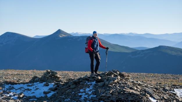 Vieja mujer atlética mochilero de pie en la cima de la montaña