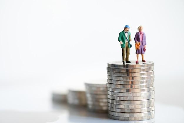 La vieja pareja figura de pie encima de las monedas de pila usando como planificación de jubilación de fondo.