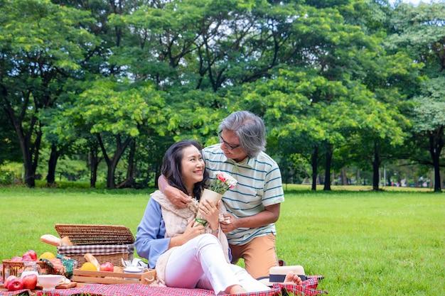 La vieja pareja se relaja en el parque. por la mañana el hombre abrazando a la mujer al lado de la cesta de picnic.