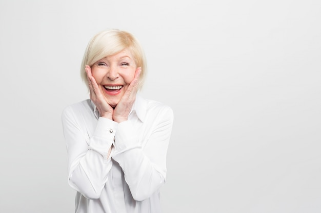 La vieja pero feliz mujer usa una blusa blanca y muestra que está muy sorprendida. ella tiene buena suerte.