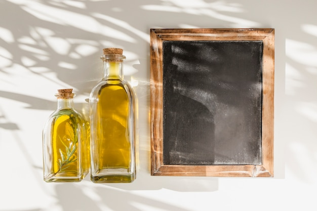 Una vieja pizarra de marco de madera en blanco con dos botellas de aceite contra la pared