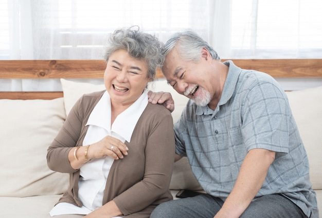 La vieja risa asiática mayor de los pares se sienta en el sofá en casa.