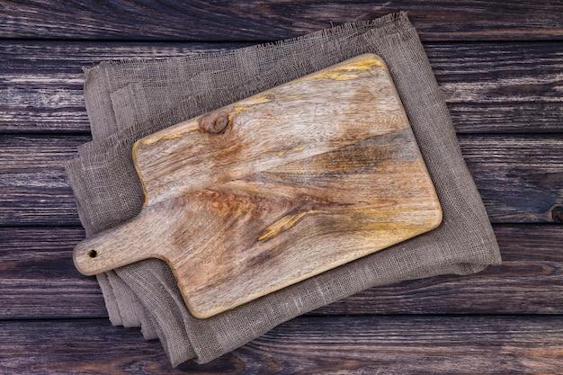Vieja tabla de cortar en la mesa de madera oscura. vista superior. copia espacio