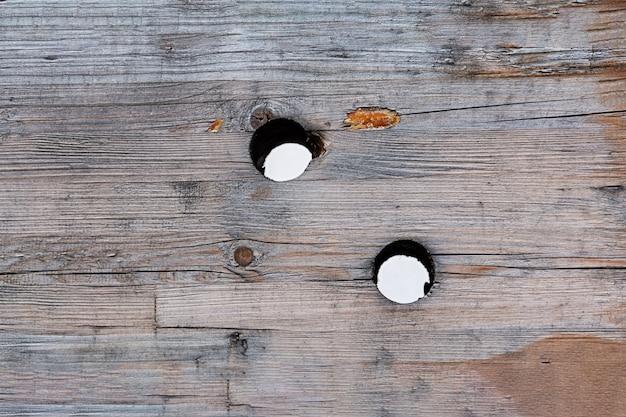 Una vieja tabla de madera con grietas y arañazos y agujeros redondos espaciados al azar. concepto de textura, interior