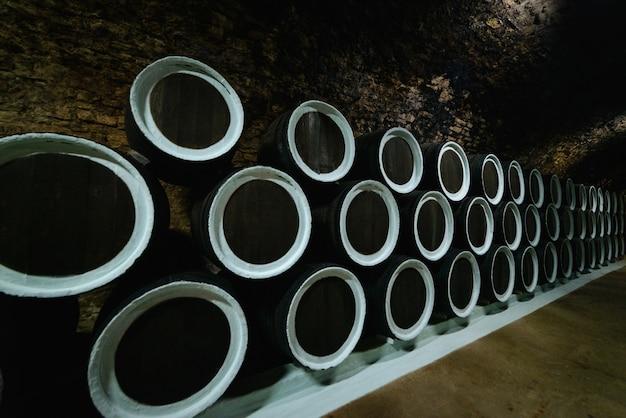 Viejas barricas de roble de vino en una bodega almacenada en una bodega