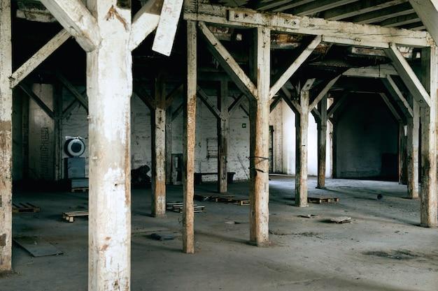 Viejas columnas de madera. antiguo almacén abandonado, iluminado por la luz de la ventana.