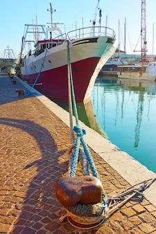 Viejo arrastrero amarrado por balizas en canal en rimini, italia
