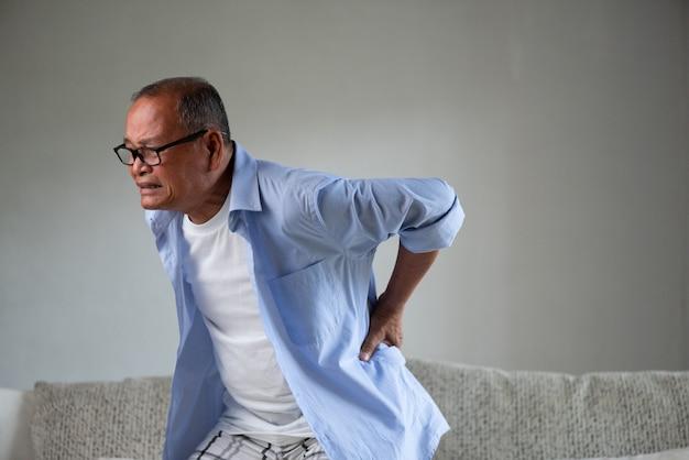 Viejo asiático sentado en el sofá y tiene un dolor de espalda