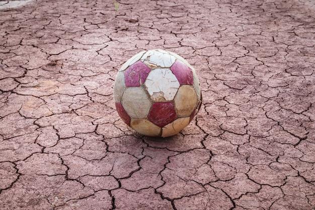 Viejo balón de fútbol en sequía