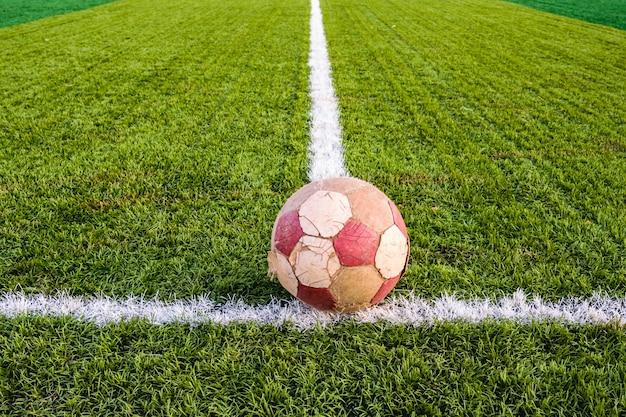 Viejo balón de fútbol sobre césped